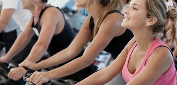 Damer som sidder på spinningcykel