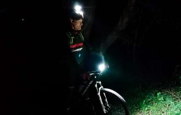 Cykelrytter i skoven med lys på cykel og hjelm